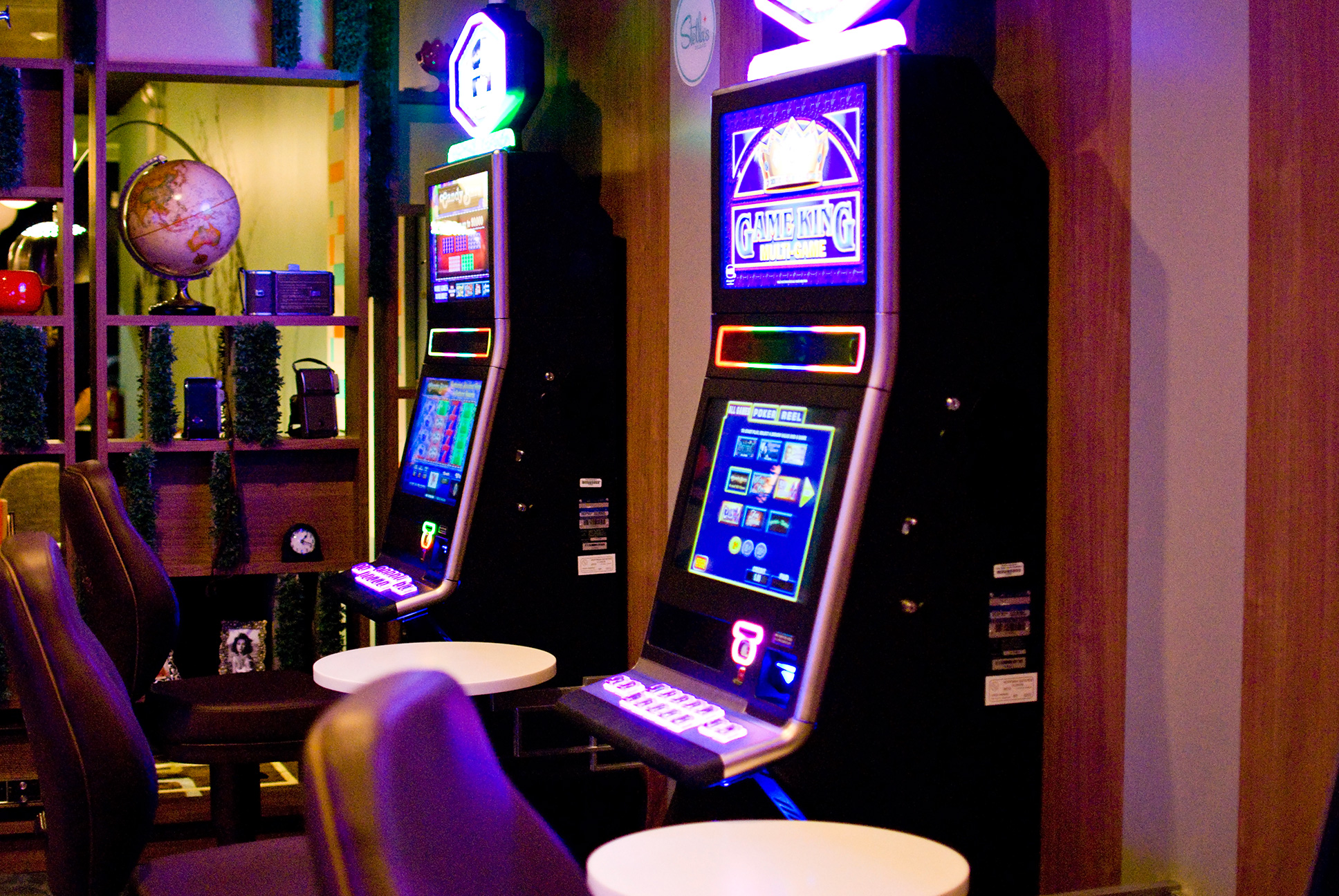 Two glowing slot machines in front of modular shelving