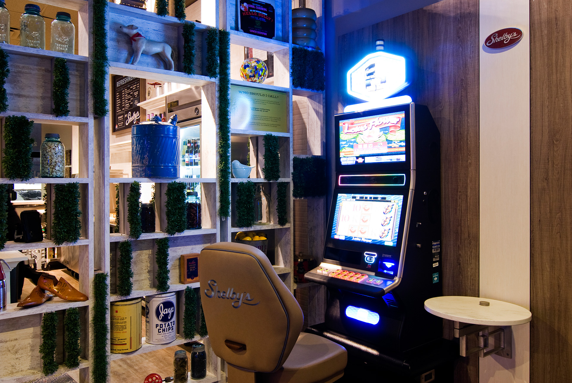 Bright lit slot machine and Shelby's branded leather chair.